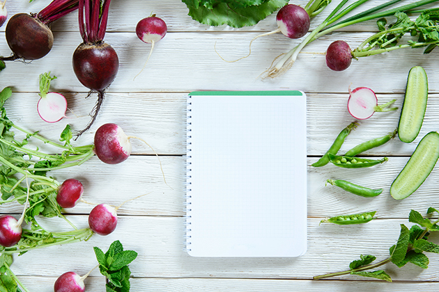 Rural white wood kitchen table with blank cook book for shopping list with salad ingredients (beets, radishes, peas, cucumber, parsley, mint). Blank recipe book, copy space